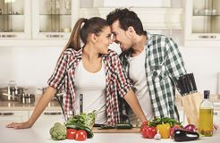 Beautiful young couple in the kitchen while cooking royalty free stock photo
