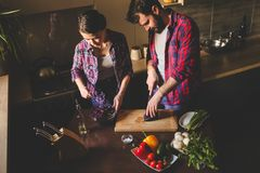 Beautiful young couple in kitchen at home while cooking healthy food. Husband cut cabbage. Wife mix salad. Scene from family life. Horizontally framed shot stock images
