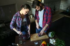 Beautiful young couple in kitchen at home while cooking healthy food. Husband cut cabbage. Wife mix salad. Scene from family life. Horizontally framed shot stock photos