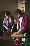 Beautiful young couple in kitchen at home while cooking healthy food. Husband cut cabbage. Wife mix salad. Scene from family life. Vertically framed shot royalty free stock images
