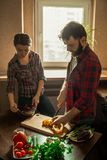 Beautiful young couple in kitchen at home while cooking healthy food. Husband cuts a pepper. Wife mix salad. Scene from family. Life. Vertically framed shot royalty free stock photo
