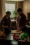 Beautiful young couple in kitchen at home while cooking healthy food. Husband cuts a pepper. Wife mix salad. Scene from family. Life. Vertically framed shot stock photography