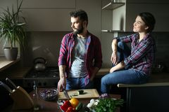 Beautiful young couple in kitchen at home while cooking healthy food. Scene from family life. Horizontally framed shot stock photos
