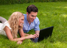 Beautiful, young couple with laptop in the grass Stock Photos