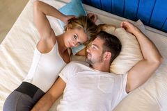Young couple cuddling on the bed. A beautiful young couple laying on the bed and cuddling stock photos