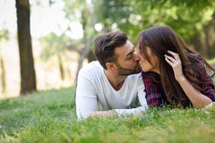 Beautiful Young Couple Laying On Grass In An Urban Park. Royalty Free Stock Photography