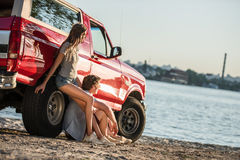 Couple with car at riverside Stock Image