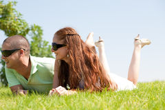 Beautiful young Couple lie down on grass. And smile royalty free stock images