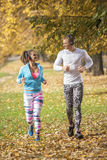 Beautiful young couple listening music and running together in the park. Autumn environment Stock Image