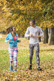 Beautiful young couple listening music and running together in the park. Autumn environment Royalty Free Stock Photography