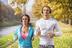 Beautiful young couple listening music and running together in the park. Autumn environment Royalty Free Stock Image