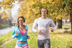 Beautiful young couple listening music and running together in the park. Autumn environment Stock Photography