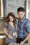 Beautiful young couple looking at color samples in model home Stock Images