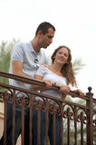 Beautiful young couple looking down from outside b. Young lovers looking down from outside balcony on an overcast afternoon making the light soft with palm trees Royalty Free Stock Photography
