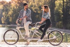 Couple with a tandem bicycle. Beautiful young couple looking at each other and smiling while riding a tandem bicycle in the park Stock Image