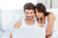 Beautiful young couple looking at laptop in bed. Happy young couple laughing at something while looking at laptop at home in bed Stock Photography