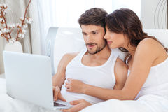 Beautiful young couple looking at laptop. Happy young couple laughing at something while looking at laptop at home Stock Photo