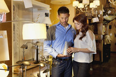 Beautiful young couple looking at lighting equipment in store Stock Image