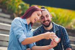 Beautiful young couple looking at the mobile phone together Royalty Free Stock Photos