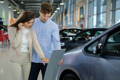 Beautiful young couple looking a new car at the dealership  showroom. Stock Image