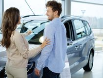 Beautiful young couple looking a new car at the dealership  showroom. Stock Photo