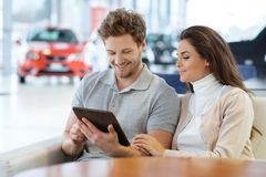 Beautiful young couple looking a new car at the dealership  showroom. Royalty Free Stock Images