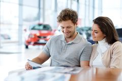 Beautiful young couple looking a new car at the dealership showroom. royalty free stock photography
