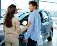Beautiful young couple looking a new car at the dealership showroom Royalty Free Stock Image