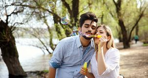 Beautiful young couple blowing soap bubbles and smiling Stock Photos