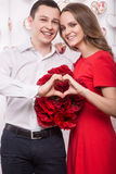 Beautiful young couple in love with a bouquet flowers showing the form of heart hands. Valentine's Day. Royalty Free Stock Photo