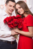 Beautiful young couple in love with a bouquet of flowers. Valentine's Day. Stock Photography