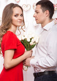 Beautiful young couple in love with a bouquet of flowers. Valentine's Day. Stock Image