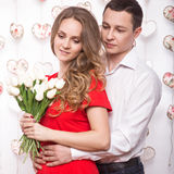 Beautiful young couple in love with a bouquet of flowers. Valentine's Day. Royalty Free Stock Photo