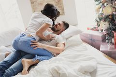 Happy couple of lovers lie on the bed and kissing. Christmas interior. Lovers together Royalty Free Stock Photo