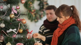 Beautiful young couple in love decorating Christmas tree, arranging the christmas lights and having fun. Christmas and New Year themes stock video