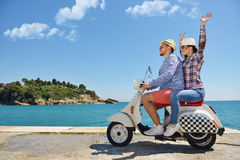 Beautiful young couple in love enjoying and having fun riding on a scooter in a beautiful nature Stock Images