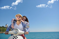 Beautiful young couple in love enjoying and having fun riding on a scooter in a beautiful nature Stock Photo