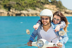 Beautiful young couple in love enjoying and having fun riding on a scooter in a beautiful nature Royalty Free Stock Photos