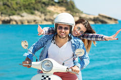 Beautiful young couple in love enjoying and having fun riding on a scooter in a beautiful nature Royalty Free Stock Photo