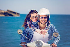 Beautiful young couple in love enjoying and having fun riding on a scooter in a beautiful nature stock image
