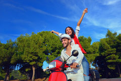 Beautiful young couple in love enjoying and having fun riding on a scooter Royalty Free Stock Photography
