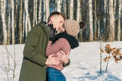 Beautiful young couple in love hugging in the park on a clear sunny winter day royalty free stock photography
