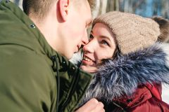 Beautiful young couple in love hugging in the park on a clear sunny winter day, close up. Boy and girl smile at each other stock photos