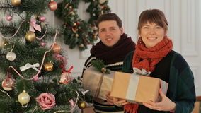 A beautiful young couple in love near the New Year tree giving presents to the viewer. Christmas and New Year themes. stock video