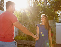 Beautiful young couple in love - Outdoors. Outdoor shot of beautiful young couple standing together holding hands and looking at each other smiling. Bright stock photos