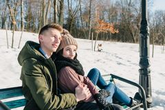 Beautiful young couple in love sitting on a park bench on a clear sunny day.The boy and the girl enjoy the warmth of the winter su. N royalty free stock image