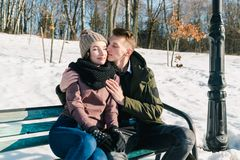 Beautiful young couple in love sitting on a park bench on a clear sunny winter day. Boy embraces and kiss his girlfriend.  stock photo