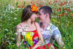 Beautiful young couple in love in the summer in a poppy field. Royalty Free Stock Photo