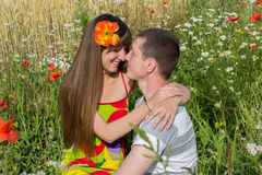 Beautiful young couple in love in the summer in a poppy field. Stock Image
