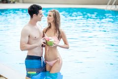 Beautiful young couple in love together in swimming pool and dri. Nking cocktails Royalty Free Stock Photography